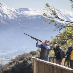 Break One Clay Target Shooting Instructor helping man fire gun with beautiful Queenstown mountains in background